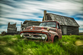 'Long exposure of clouds drifting by over an abandoned truck and house in a rural area; Saskatchewan, Canada'