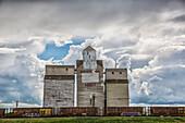 'Rural grain elevator with cumulonimbus clouds building up around it; Saskatchewan, Canada'