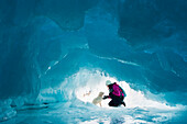 'Woman with her pet dog inside a natural ice cave on frozen Lake Superior in winter; Ontario, Canada'