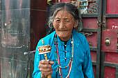 'Elderly woman spins prayer wheel; Manigange, Sichuan, China'