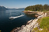 Sailboat passing Perry Island in Prince William Sound, Southcentral Alaska.