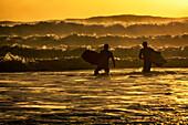 Body surfers on the coast of Kodiak Island during late afternoon, Pasagshak State Park, Kodiak Island, Alaska