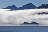 A cruise ship, the Zaandam Holland America, travels along the edge of a fog bank in Taku Inlet on its way to Juneau, Southeast Alaska