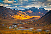 Sunset lighting Brooks Range at Chandalar Shelf, viewed from Atigun Pass between Gates of the Arctic National Park & preserve and Arctic National Wildlife Refuge with Dalton Hwy and pipeline cutting through the valley. Arctic Alaska, Autumn.