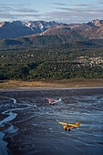Super Cub airplanes fly over Turnagain Arm with Seward Highway, Anchorage hillside and the Chugach Mountains in the background, Southcentral Alaska