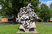 couple d'amoureux perche sur une statue de siegfrid wolske representant le visage du compositeur allemand ludwig van beethoven, bonn, land de rhenanie-du-nord-westphalie, allemagne