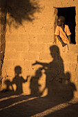 child and earthen houses in the village of toucouleur de deguembere, fanaye dieri province, senegal, west africa