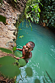 Boy jumping from rocks into the water, forest is part of the Ram Krishna Pur Dam, reservoir inland near Butler Bay Beach, northern Can Hat Bay, Little Andaman, Andaman Islands, Union Territory, India