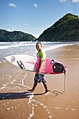 Surfer Rafael, 100% Jesus lettering on his board, Praia do Tombo, in the west of the city, Guaruja, Costa Verde, Sao Paulo, Brazil