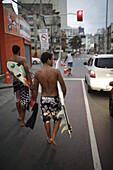 Surfers in the evening, coming from the beach on Avenida Oceanica, Barra, Salvador de Bahia, Bahia, Brazil