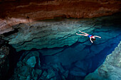 Luiza Voll from Sao Paulo bathing in Poco Azul, sunbeam, underground river, archaeological site, east of the Chapada Diamantina National Park, Andarai, Bahia, Brazil