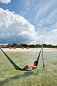 Lagoa do Paraiso, visitor bathing in a hammock at the resort Chez Loran, lagoon near Jericoacoara, Ceara, Brazil