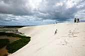 On the Tatajuba sand dunes, boys from the village rent homemade sandboards to visitors, lagoons are filled by rainwater, Tatatjuba, west Jericoacoara, Ceara, Brazil