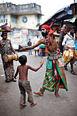 ' Nadoni - ''run from the place'', gypsies, juggler family between market stalls, mother drumming, son dancing and collecting money, father whipping and scourging himself, Hindus, in Valparai, Tamil Nadu, Western Ghats, India'