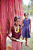 Christian girl in front of drying fishing nets which are hanging between palm trees, fishing huts in Mararikulam, south of Kochi, Kerala, India