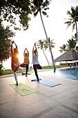 Yoga class with teacher at the pool in the evening, in front of Restaurant and under palm trees, Erandia Marari, Ayurveda Beach Resort, Mararikulam, south of Kochi, Kerala, India