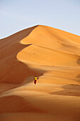 Sultanate of OMAN the Rub al Khali desert, a lonely man is walking towards a very high sand dune