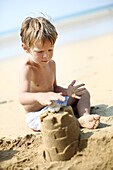 Little boy making a sand castle on the beach