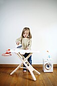A 3 years old girl playing with an iron and ironing board for child