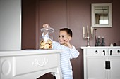 A little boy taking some cookies in a jar