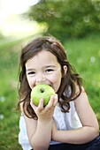 A 5 years old girl eating an apple in the countryside