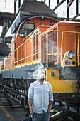 Caucasian man blowing smoke in train yard