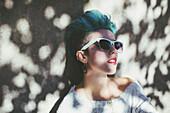 Stylish Caucasian woman wearing sunglasses in shade