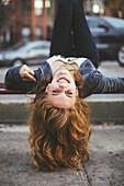 Caucasian woman laying on city sidewalk