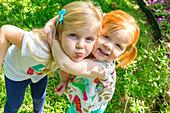 Caucasian sisters hugging in backyard