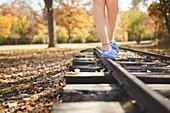 Caucasian girl balancing on train tracks