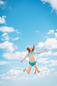 Caucasian girl jumping for joy in blue sky