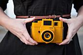 Close up of Black woman holding plastic camera