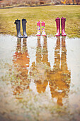 Reflection of people from rain boots in puddle