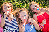 Girls eating flavored ice in grass
