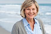 Smiling Caucasian woman walking on beach