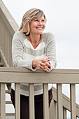 Smiling Caucasian woman standing staircase banister