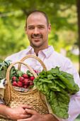 Caucasian man carrying basket of fresh produce