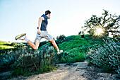 Caucasian athlete running on rural trail