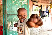 Boy laughing, showing a fist, Kigamboni, Tanzania, Africa