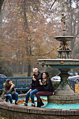 3 girls eating ice cream at the fountain in autumn, Hamburg, Germany, Europe
