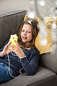 Girl listening to music at home on her smartphone, Hamburg, Germany, Europe