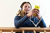 Girl listening to music at home on her smartphone, Hamburg, Germany, Europe