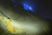 Burning sulfur and blue flames of the volcano Ijen at night. Pipe transferring hot sulfur gases for cooling down. Sulfur depositing in solid form, East Java, Ijen volcano, Indonesia