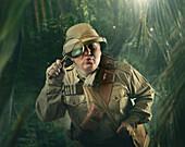 Caucasian hunter peering through magnifying glass in jungle