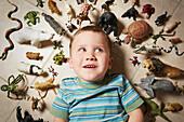 Caucasian boy surrounded near toy animals