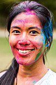 Smiling Asian woman covered in pigment powder