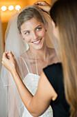 Caucasian bridesmaid arranging veil for bride