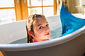Caucasian girl wearing mermaid tail in bath