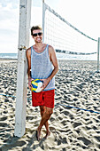 Caucasian man holding volleyball on beach