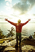 Man standing with arms outstretched on rocks over ocean